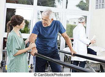 patiënt, kijken naar, vrouwlijk, fysiotherapeut, terwijl het lopen, tussen
