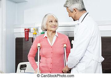 patiënt, met, krukken, kijken naar, arts, in, rehab, centrum