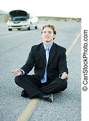 patience - business man meditates while waiting along a...