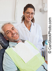 Patient and dentist smiling at camera