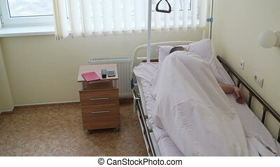 Patient at a hospital lying on a bed in his room, resting and sleeping after the surgery