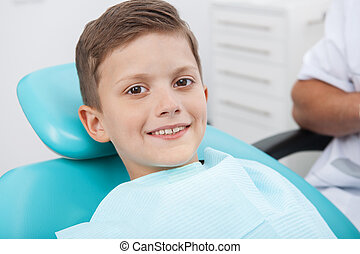 Patient at dentist office. Cheerful little boy sitting at the chair in dental office and smiling