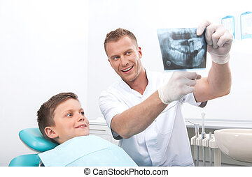 Patient at dentist office. Cheerful little boy sitting at the chair in dental office while doctor showing something at X-ray photo