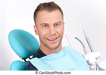 Patient at dentist office. Cheerful young man sitting at the chair in dental office and smiling