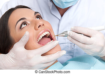 Patient at dentist office. Close-up of beautiful young woman sitting at the chair in dental office and doctor examining teeth