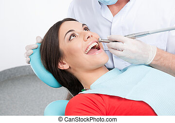 Patient at dentist office. Top view of beautiful young woman sitting at the chair in dental office and doctor examining teeth