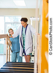 Patient Being Assisted By Physical Therapist In Moving Upstairs