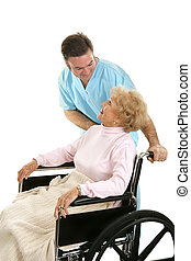 Doctor or male nurse caring for a senior woman in a wheelchair. Isolated on white.