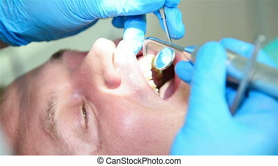 Patient Dental Checkup - Dentist Examining Patient With...
