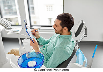 patient filling application form at dental clinic