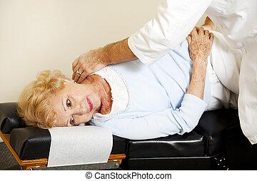 Patient Gets Chiropractic Adjustment - Senior woman getting...