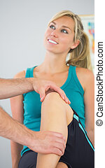 Patient having knee examined by physiotherapist