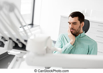 patient having toothache at dental clinic office