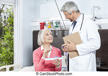Patient Holding Medicine Organizer While Looking At Doctor -...