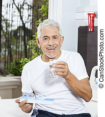 Patient Holding Pill Organizer And Water Glass In Rehab Center