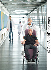 patient in a wheelchair pushed by doctor in hospital