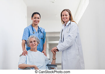 Patient in corridor holding hand of a doctor