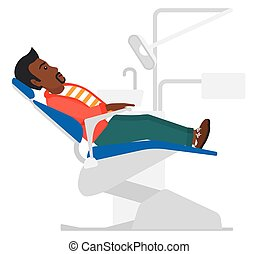 Patient in dental chair. - An african-american patient...