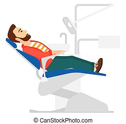 Patient in dental chair. - A patient sitting in dental chair...
