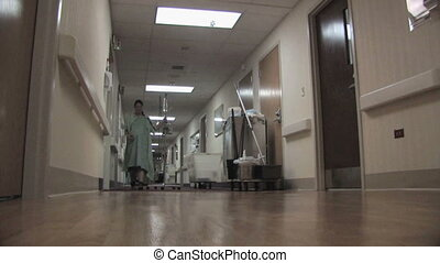 Patient in Hospital Hallway - A pregnant woman walks down a...