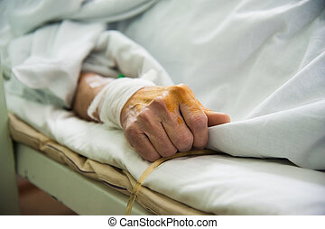 Patient in hospital ward - Focus on the hand of a patient in...