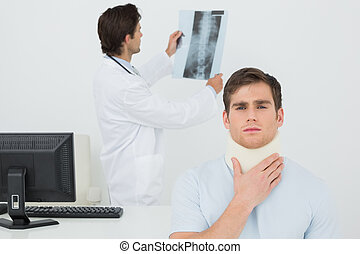 Patient in surgical collar with male doctor examining spine x-ray in background at medical office