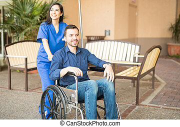Patient in wheelchair going for stroll - Handsome male...