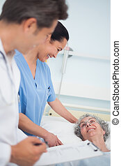 Patient laughing with a nurse and a doctor in hospital ward