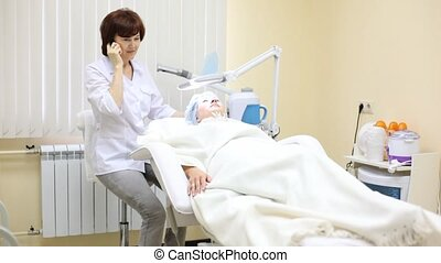 Patient lies in cosmetology armchair and cosmetician speaks by phone
