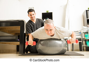 Patient Lifting Dumbbells While Lying On Exercise Ball By Physiotherapist