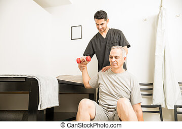 Patient Lifting Weights With Help Of Therapist In Physiotherapy Clinic