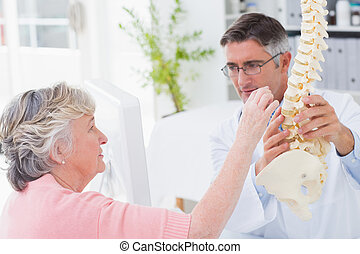 Patient looking at anatomical spine while doctor explaing...