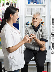 Patient Looking At Female Doctor Checking His Sugar Level