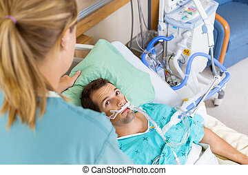 Patient Looking At Nurse As She Adjusts His Pillow
