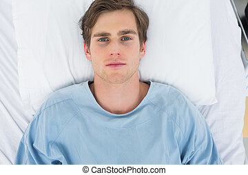 Overhead view of male patient lying in hospital bed