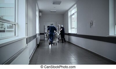 Patient on stretcher pushed at speed through a hospital corridor by doctors