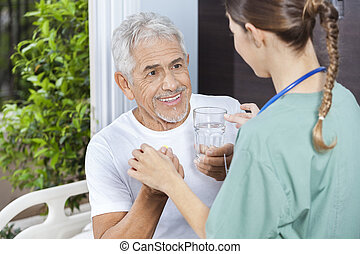 Patient Receiving Medicine And Water Glass From Female Nurse