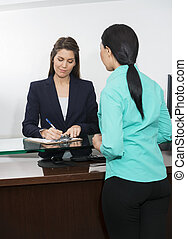 Patient Registering To Receptionist At Counter In Hospital