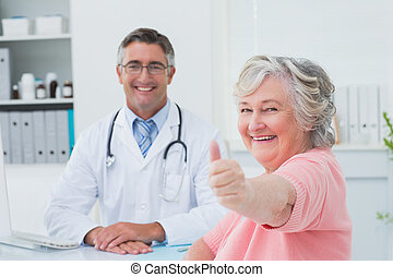 Patient showing thumbs up sign while sitting with doctor -...