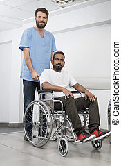 Patient Sitting In Wheelchair While Nurse Standing At Hospital