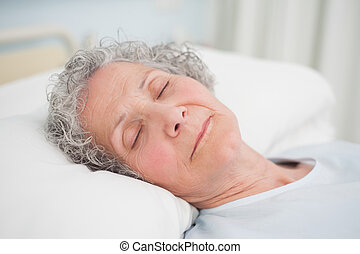 Patient sleeping on a medical bed in hospital ward