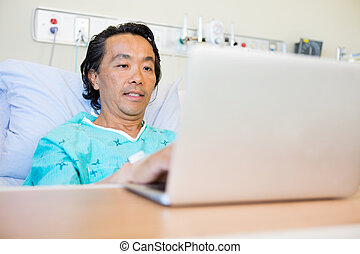 Patient Using Laptop On Hospital Bed
