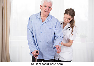 Patient using walking stick assisted by doctor