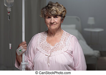 Patient walking with drip stand - Elder female patient ...