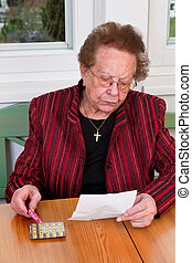 Patient with a drug Beipacktext - Old Woman with tablets and...