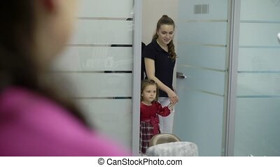 Patient with child entering to dental clinic doctor