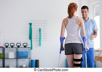 Patient with crutches during a rehabilitation with her physiotherapist in a clinic