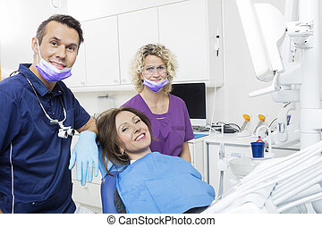 Patient With Dentist And Assistant At Clinic