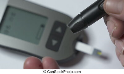 Patient with diabetes using blood glucose meter and diabetic...