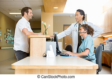 Patient With Doctor And Nurse At Reception Desk - Male...